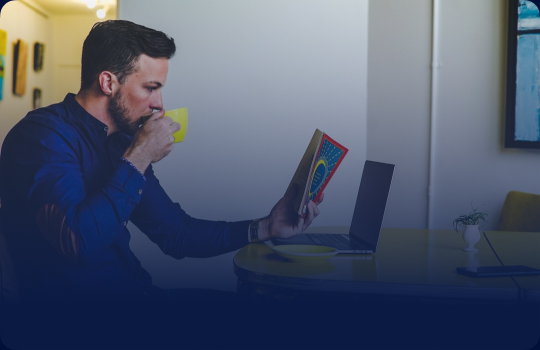 Image of a man drinking a hot drink and reading a book.